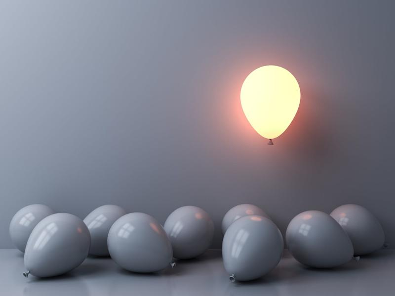 Gray balloons with one lit-up one rising above them