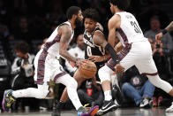 Brooklyn Nets guard Kyrie Irving, left, drives pas Atlanta Hawks guard Brandon Goodwin (0) as Nets center Jarrett Allen (31) defends Parsons during the first half of an NBA basketball game, Sunday, Jan. 12, 2020, in New York. (AP Photo/Kathy Willens)