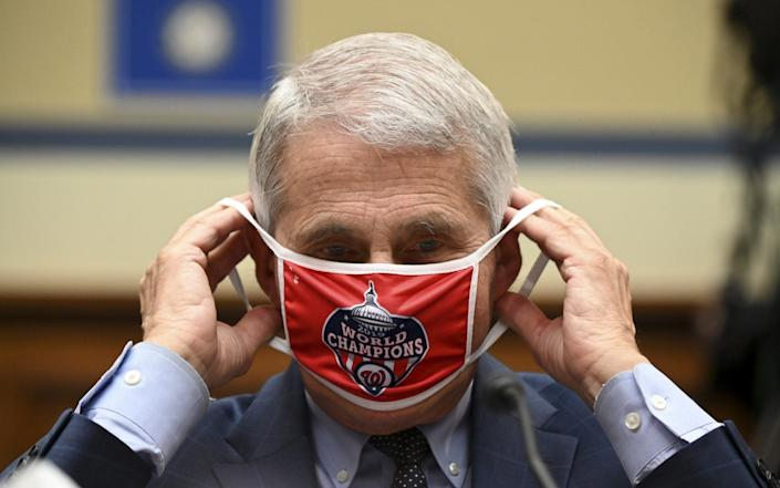 Anthony Fauci, director of the National Institute of Allergy and Infectious Diseases, removes his Washington Nationals protective mask during a Congress committee meeting on the coronavirus crisis - Getty Images North America
