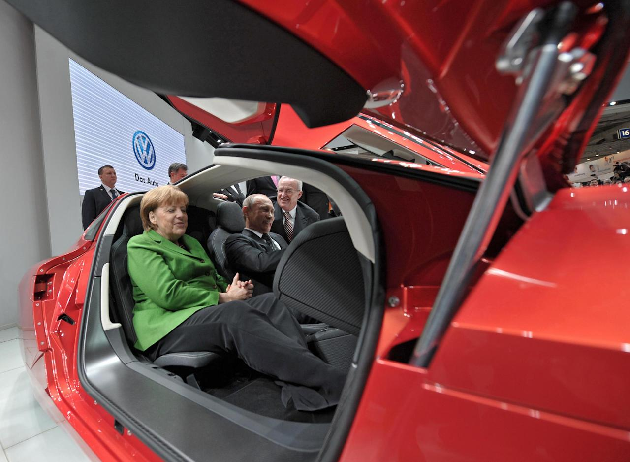 German Chancellor Angela Merkel, left, and Russian President Vladimir Putin, right, visit the Hannover Fair, in Hannover, central Germany, on Monday, April 8, 2013. (AP Photo/RIA Novosti, Alexei Druzhinin, Presidential Press Service)