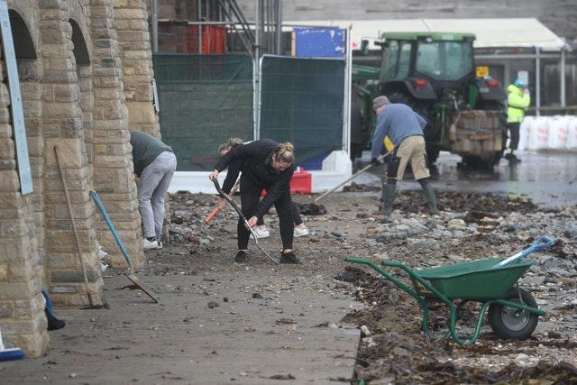 People clean up stones brought in by the sea in Swanage