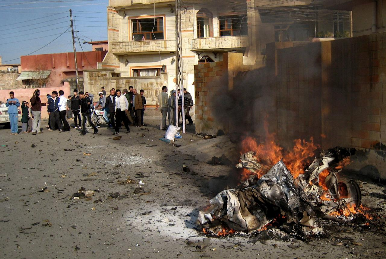 Iraqis inspect the scene of a bomb attack in Kirkuk, 180 miles (290 kilometers) north of Baghdad, Iraq, Tuesday, Nov. 27, 2012. Three parked car bombs exploded Tuesday morning simultaneously in the city of Kirkuk, home to a combustible mix of Kurds, Sunni Arabs and Turkomen who all claim rights to the city, killing and wounding scores of people, police said. (AP Photo/Emad Matti)