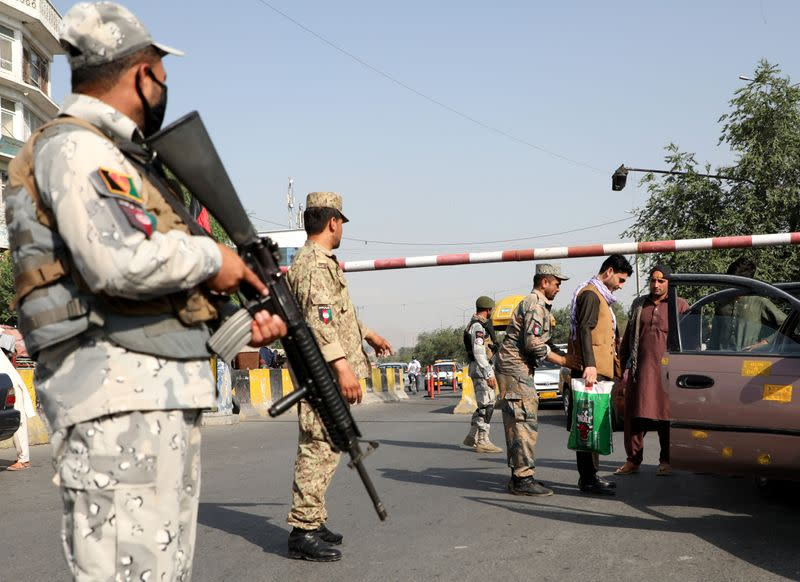 Afghan policemen stand guard at a check point in Kabul, Afghanistan