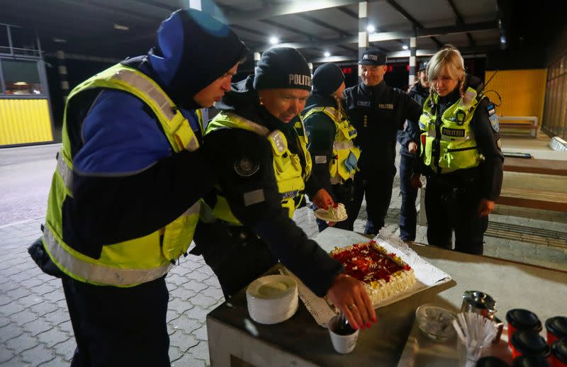 Estonian police and border guard officers pick pieces of cake at border crossing point in Ikla