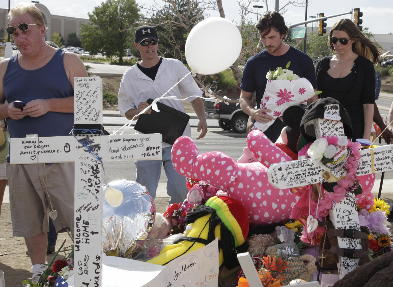 "Actor Christian Bale and his wife Sibi Blazic, at right, carry flowers to place on a memorial to the victims of Friday's mass shooting, Tuesday, July 24, 2012, in Aurora, Colo. Twelve people were killed when a gunman opened fire during a late-night showing of the movie ""The Dark Knight Rises,"" which stars Bale as Batman. (AP Photo/Ted S. Warren)"