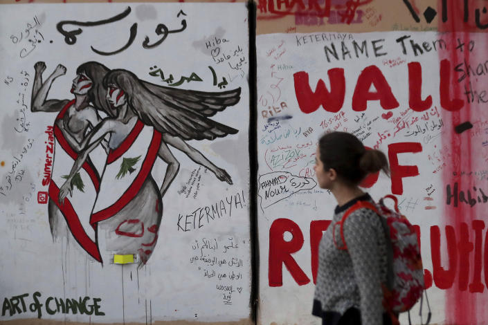 """In this Tuesday, Nov. 26, 2019 photo, a woman looks at a wall at United Nations Headquarters, decorated with graffiti in Arabic that reads, """"Revolution is a woman, and Oh freedom,"""" during ongoing protests, in Beirut, Lebanon. Lebanon's wave of anti-government protests has given a new platform for women struggling against religious laws. Under Lebanon's sectarian system, sects have the power to set the rules for marriage, divorce and custody of children for their communities. (AP Photo/Hassan Ammar)"""