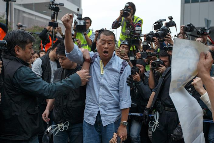 Lai shouts a slogan before he is taken away by a police officer outside the government headquarters in Hong Kong on December 11, 2014.