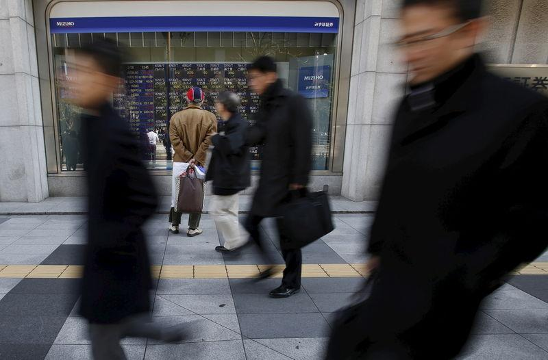 A pedestrian looks at various stock prices outside a brokerage in Tokyo, Japan, February 26, 2016. REUTERS/Yuya Shino/File Photo