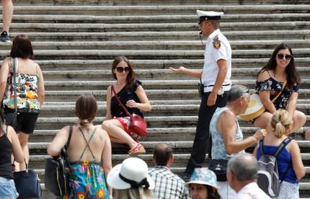 A municipal policeman asks a tourist to rise from Rome's Spanish Steps