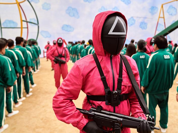 """A triangle pink jacket with a gun in """"Squid Game"""""""
