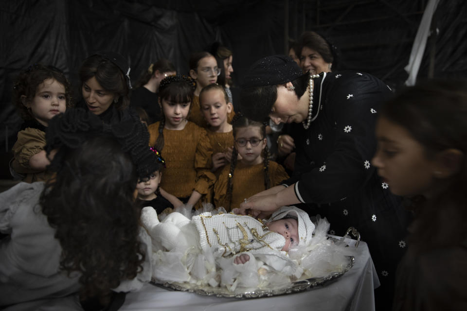"""Ultra-Orthodox Jewish women adorn 30-day-old Yossef Tabersky, the great grandchild of the chief rabbi of the Lelov Hassidic dynasty, during the """"Pidyon Haben"""" ceremony in Beit Shemesh, Israel, Thursday, Sept. 16, 2021. The Pidyon Haben, or redemption of the firstborn son, is a Jewish ceremony hearkening back to the biblical exodus from Egypt. (AP Photo/Oded Balilty)"""