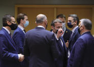 French President Emmanuel Macron, center, speaks with Hungary's Prime Minister Viktor Orban, right, during a round table meeting at an EU summit in Brussels, Thursday, Dec. 10, 2020. European Union leaders meet for a year-end summit that will address anything from climate, sanctions against Turkey to budget and virus recovery plans. Brexit will be discussed on the sidelines. (AP Photo/Olivier Matthys, Pool)