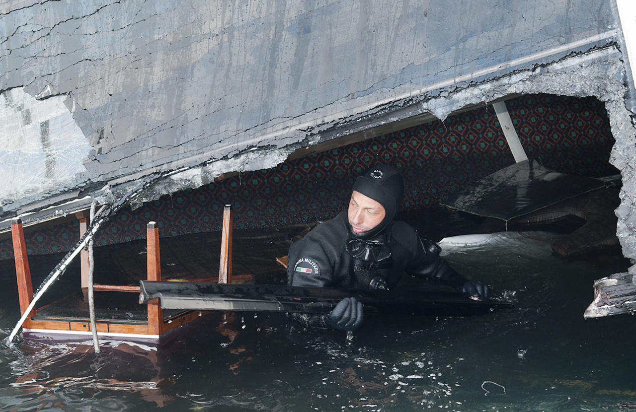 In this undated photo released by the Italian Navy Tuesday, Jan. 24, 2012, a scuba diver makes his way into a flooded cabin of the Costa Concordia cruise ship grounded off the Tuscan island of Giglio, Italy. A large platform carrying a crane and other equipment hitched itself to the toppled Costa Concordia on Tuesday, signaling the start of preliminary operations to remove a half-million gallons of fuel from the grounded cruise ship before it leaks into the pristine Tuscan sea. Actual pumping of the oil isn't expected to begin until Saturday, but officials from the Dutch shipwreck salvage firm Smit were seen on the bow of the Concordia and in the waters nearby making preparations to remove the fuel, while the search for missing passengers continues. (AP Photo/Italian Navy GOS)
