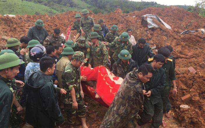 Army officers carry a body recovered from a landslide in Quang Tri province, - VNA
