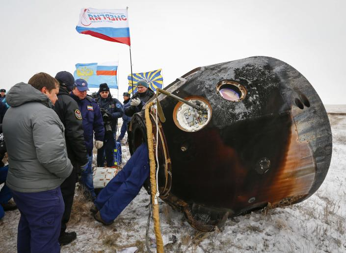 REFILE - CLARIFYING DATE OF LANDING IN SECOND SENTENCE Ground personnel work next to the Soyuz TMA-13M capsule of the International Space Station (ISS) crew of Alexander Gerst of Germany, Maxim Suraev of Russia and Reid Wiseman of the U.S. after its landing near the town of Arkalyk in northern Kazakhstan November 10, 2014. A veteran Russian cosmonaut and two International Space Station crewmates, one from the United States and one from Germany, returned safely to Earth on Monday with a parachute landing of their Soyuz capsule in Kazakhstan, ending 5-1/2 months in orbit. REUTERS/Shamil Zhumatov (KAZAKHSTAN - Tags: SCIENCE TECHNOLOGY)