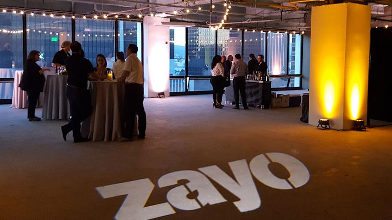 Office space with several people and festive lighting, and Zayo logo on the floor.