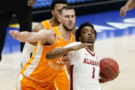 Alabama's Herbert Jones (1) drives against Tennessee's Uros Plavsic (33) in the first half of an NCAA college basketball game in the Southeastern Conference Tournament Saturday, March 13, 2021, in Nashville, Tenn. (AP Photo/Mark Humphrey)