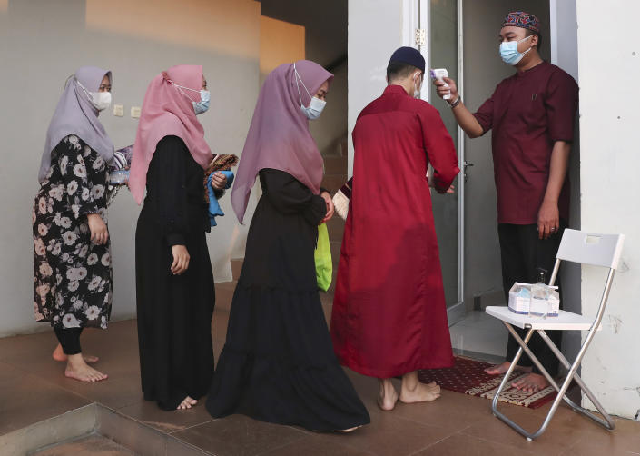 An official takes the body temperature reading of worshippers arriving for an Eid al-Adha prayer as to curb the spread of coronavirus during an Eid al-Adha prayer at Zona Madina mosque in Bogor, Indonesia,Tuesday, July 20, 2021. Muslims across Indonesia marked a grim Eid al-Adha festival for a second year Tuesday as the country struggles to cope with a devastating new wave of coronavirus cases and the government has banned large gatherings and toughened travel restrictions. (AP Photo/Tatan Syuflana)