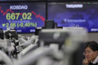 A currency trader watches computer monitors near the screen showing the Korean Securities Dealers Automated Quotations (KOSDAQ), left, at the foreign exchange dealing room in Seoul, South Korea, Thursday, Nov. 7, 2019. Asian stocks are mostly lower after a meandering day of trading left U.S. stock indexes close to their record highs. (AP Photo/Lee Jin-man)