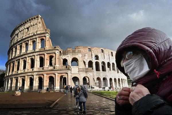 A man wearing a protective mask passes by the Coliseum in Rome on March 7, 2020 amid fear of Covid-19 epidemic.