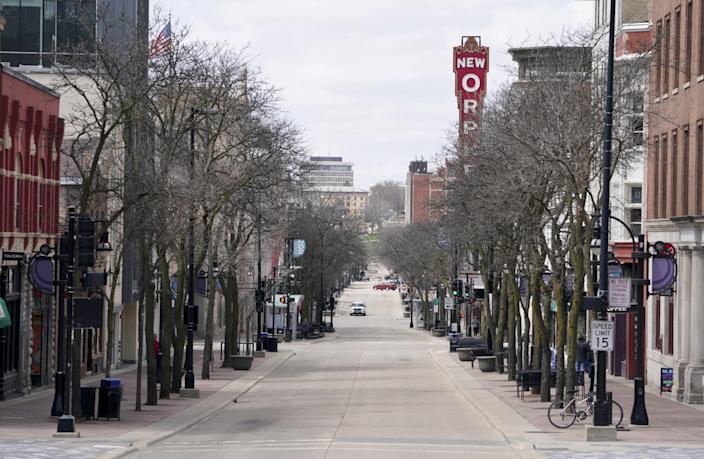 In this Wednesday April 15, 2020, photo, State Street is mostly empty around noontime due to the coronavirus pandemic in Madison, Wis.