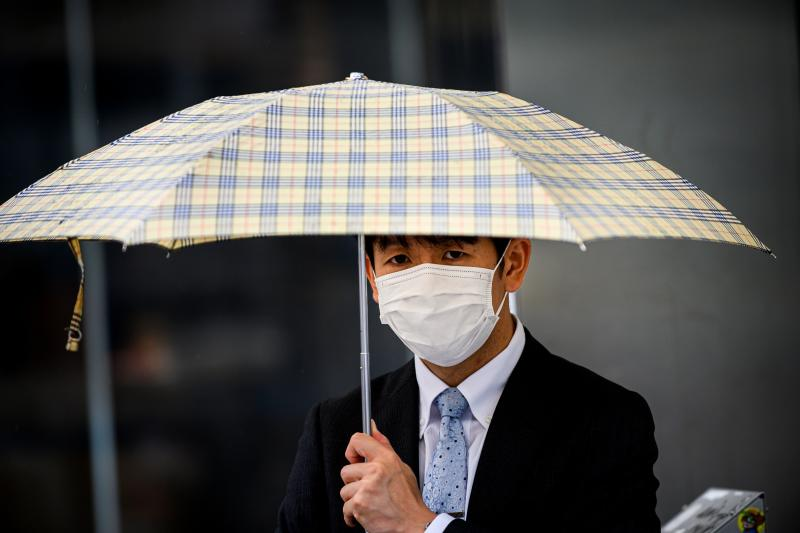 A man wearing a facemask amid concerns over the spread of the COVID-19 coronavirus holds his umbrella as he walks in the Shibuya district of Tokyo on May 26, 2020, a day after the Japanese government lifted a nationwide state of emergency. - Japan lifted a nationwide state of emergency over the coronavirus on May 25, gradually reopening the world's third-largest economy as government officials warned caution was still necessary to prevent another wave. (Photo by Behrouz MEHRI / AFP) (Photo by BEHROUZ MEHRI/AFP via Getty Images)