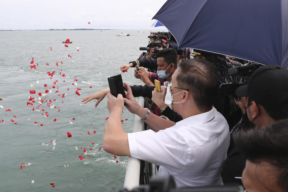 Relatives of the victims of a Sriwijaya Air Flight 182 throw flowers into the Java Sea where the plane crashed on Jan. 9 killing all of its passengers, during a memorial ceremony held on the deck of Indonesian Navy Ship KRI Semarang, near Jakarta in Indonesia, Friday, Jan. 22, 2021. (AP Photo/Tatan Syuflana)