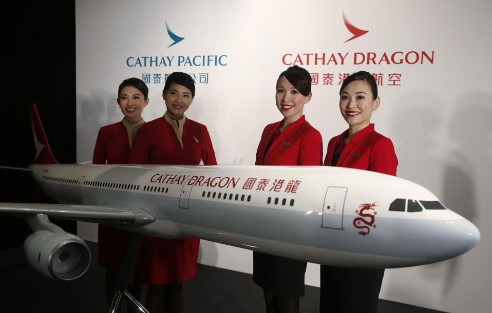 FILE - In this Jan. 28, 2016, file photo, flight attendants pose next to a model jet decorated in the new livery of Hong Kong airline Cathay Dragon, formerly known as Dragonair in Hong Kong. Cathay Pacific Airways said Wednesday, March 9, 2016, that its annual profit nearly doubled in 2015 as passenger demand grew and tumbling oil prices cut its fuel bill. Hong Kong's biggest airline said that net income jumped 90.5 percent from the year before to 6 billion Hong Kong dollars ($773 million). (AP Photo/Kin Cheung, File)
