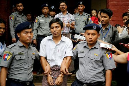 FILE PHOTO: Detained Reuters journalist Kyaw Soe Oo and Wa Lone are escorted by police as they leave after a court hearing in Yangon, Myanmar, Aug. 20, 2018. REUTERS/Ann Wang/File Photo