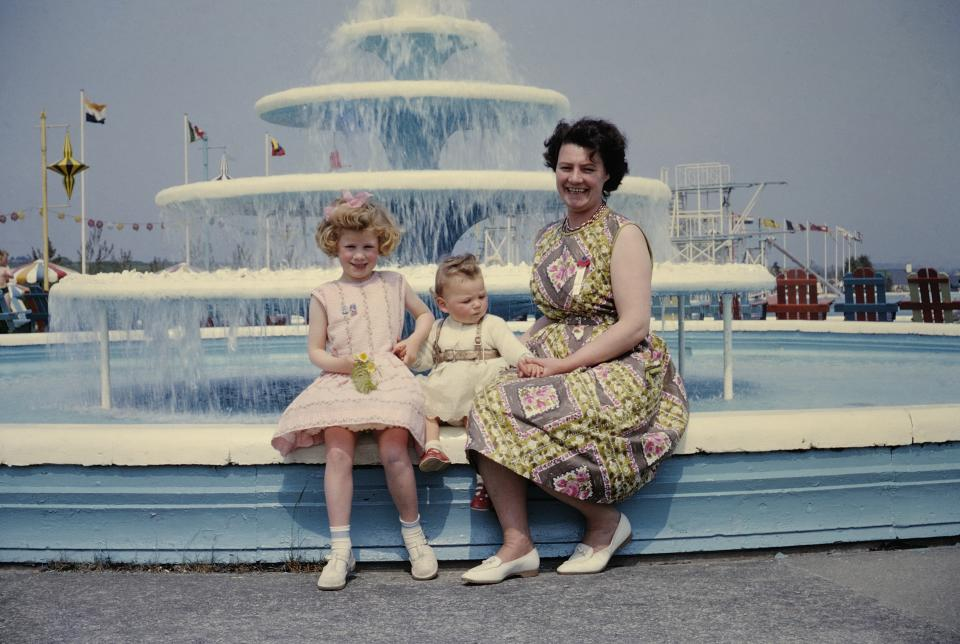 Mother and two daughters sitting by fountain at holiday camp in Wales.