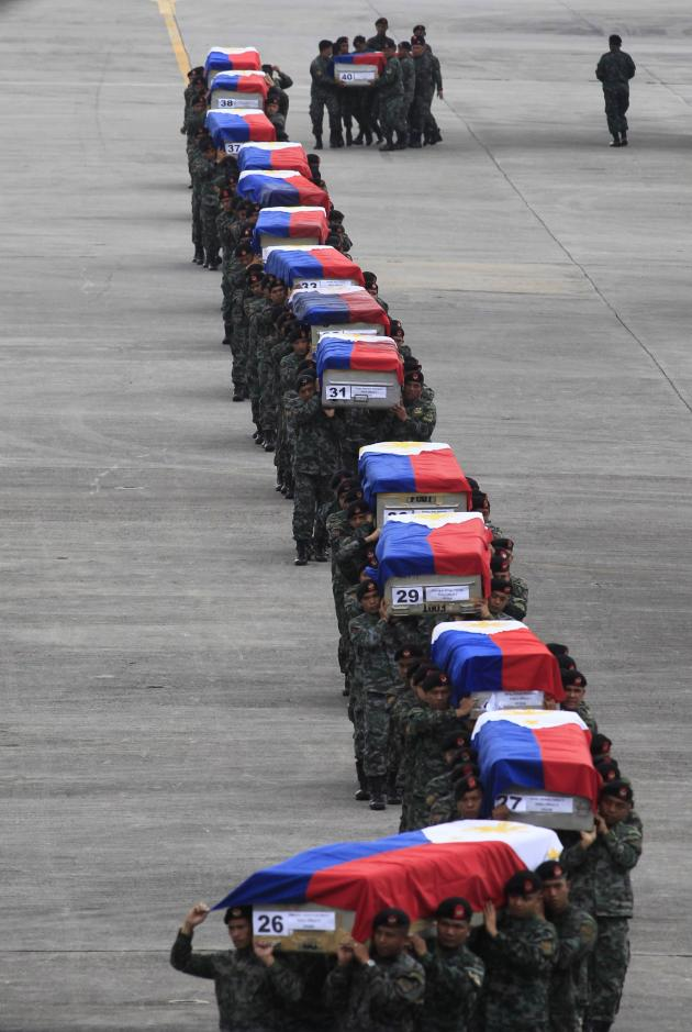 """Members of the Philippine National Police's (PNP) Special Action Force (SAF) unit carry metal caskets containing the bodies of slain SAF police who were killed in Sunday's clash with Muslim rebels, upon arriving at Villamor Air Base in Pasay city, metro Manila January 29, 2015. Philippine President Benigno Aquino urged legislators on Wednesday not to abandon a plan for autonomy for Muslims to end a decades-old insurgency after the clash in which dozens of people were killed, saying doing so would dash hopes for peace.A top official described the clash on Sunday, which shattered a three-year ceasefire, as a """"misencounter"""" during a bid to arrest two militants who had taken refuge with Moro Islamic Liberation Front (MILF) fighters. REUTERS/Romeo Ranoco (PHILIPPINES - Tags: POLITICS CRIME LAW MILITARY TPX IMAGES OF THE DAY)"""