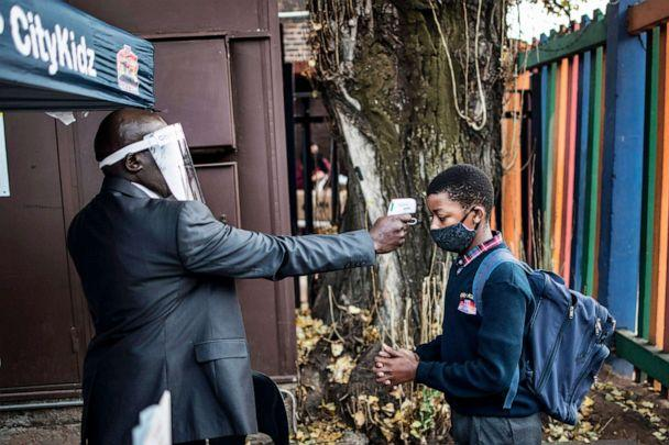 PHOTO: A pupil at the City Kidz Pre & Primary School has his temperature taken as he enters the school premises in the Inner City district of Johannesburg, South Africa, on June 1, 2020. (Marco Longari/AFP via Getty Images)