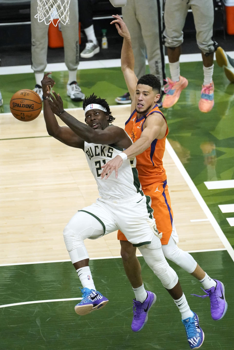Milwaukee Bucks guard Jrue Holiday (21) fights for a rebound with Phoenix Suns guard Devin Booker, right, during the second half of Game 4 of basketball's NBA Finals in Milwaukee, Wednesday, July 14, 2021. (AP Photo/Paul Sancya)
