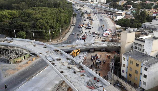 Rescue workers try to reach vehicles trapped underneath a bridge that collapsed while under construction in Belo Horizonte July 3, 2014. An unfinished overpass collapsed in the Brazilian World Cup host city of Belo Horizonte on Thursday, killing at least two people, emergency officials said. REUTERS/Carlos Greco-DYN (BRAZIL - Tags: DISASTER SPORT SOCCER WORLD CUP BUSINESS CONSTRUCTION TPX IMAGES OF THE DAY) ARGENTINA OUT. NO COMMERCIAL OR EDITORIAL SALES IN ARGENTINA