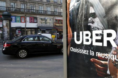 File photo shows a taxi passing by an advertisement for the Uber car and ride-sharing service displayed on a bus stop in Paris