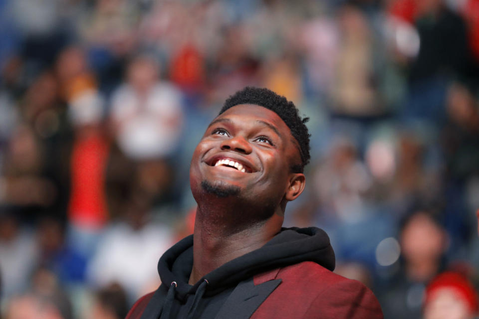 New Orleans Pelicans forward Zion Williamson watches the video screen during a player introduction video before the team's NBA basketball game against the Denver Nuggets in New Orleans, Thursday, Oct. 31, 2019. The rookie first round draft pick is recovering from knee surgery. (AP Photo/Gerald Herbert)