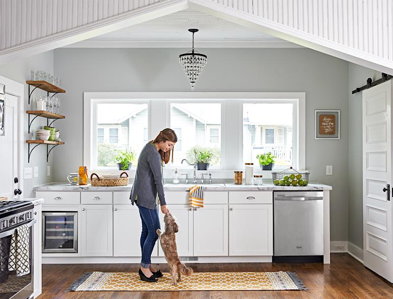 woman and dog in grey kitchen with three windows