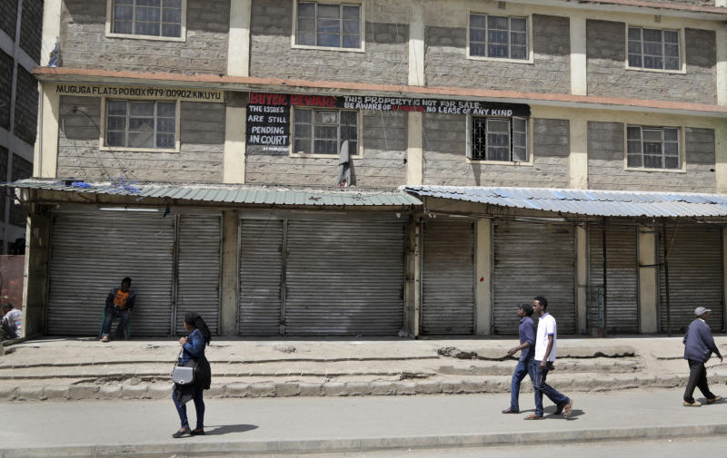 Kenyans walk past closed shops in the Eastleigh area of the capital, after members of the business community there closed the shops as a protest to condemn Tuesday's attack on a hotel complex, in Nairobi, Kenya, Friday, Jan. 18, 2019. Extremists stormed a luxury hotel complex in Kenya's capital on Tuesday, setting off explosions and gunning down people at cafe tables in an attack claimed by militant group al-Shabab. (AP Photo/Khalil Senosi)