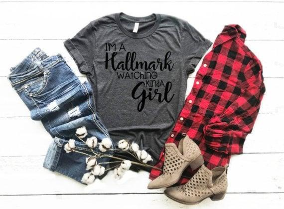 """<p>Let your favorite Hallmark fans wear their love loud and proud with this <a href=""""https://www.popsugar.com/buy/Im-Hallmark-Watching-Kinda-Girl-Shirt-395681?p_name=I%27m%20a%20Hallmark%20Watching%20Kinda%20Girl%20Shirt&retailer=etsy.com&pid=395681&price=20&evar1=buzz%3Aus&evar9=45555300&evar98=https%3A%2F%2Fwww.popsugar.com%2Fentertainment%2Fphoto-gallery%2F45555300%2Fimage%2F45555368%2FIm-Hallmark-Watching-Kinda-Girl-Shirt&prop13=mobile&pdata=1"""" rel=""""nofollow"""" data-shoppable-link=""""1"""" target=""""_blank"""" class=""""ga-track"""" data-ga-category=""""Related"""" data-ga-label=""""http://www.etsy.com/listing/626229950/im-a-hallmark-watching-kinda-girl?ga_order=most_relevant&amp;ga_search_type=all&amp;ga_view_type=gallery&amp;ga_search_query=hallmark&amp;ref=sr_gallery-2-7&amp;organic_search_click=1&amp;frs=1"""" data-ga-action=""""In-Line Links"""">I'm a Hallmark Watching Kinda Girl Shirt</a> ($20). </p>"""