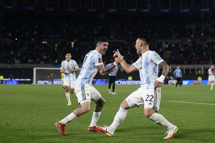 Argentina's Lautaro Martinez (22) celebrates with teammates Rodrigo De Paul after scoring his side's third goal against Uruguay during a qualifying soccer match for the FIFA World Cup Qatar 2022 in Buenos Aires, Argentina, Sunday, Oct. 10, 2021. (AP Photo/Gustavo Garello)