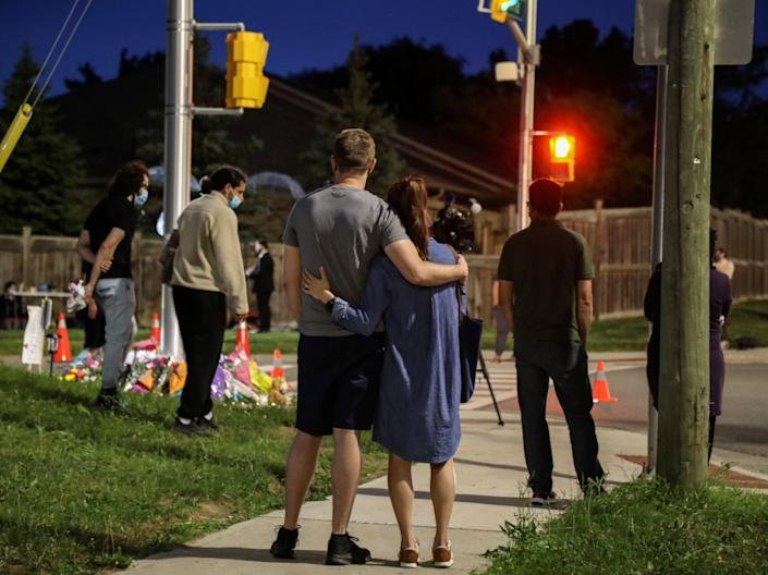 People gathered at a temporary monument after four family members were struck killed by a truck in London, Ontario (Carlos Osorio / Reuters)