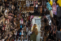 A shopkeeper arranges shoes during a partial relaxation of restrictions to curb the spread of coronavirus in Gauhati, India, Wednesday, June 9, 2021. (AP Photo/Anupam Nath)