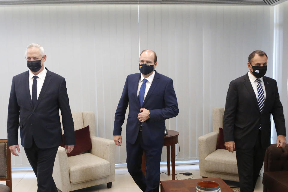 Cyprus' Defense Minister Charalambos Petrides, center, meets with his Israeli counterpart Benny Ganz, left, on his first visit to Cyprus and his Greek counterpart Nikolaos Panagiotopoulos, right, ahead of their meeting aimed at bolstering defense ties in the Cypriot capital Nicosia, Cyprus, on Thursday, Nov. 12, 2020. Greece, Cyprus and Israel have in recent years forged a closer partnership that they say aims to strengthen security and stability in the eastern Mediterranean. (AP Photo/Petros Karadjias)