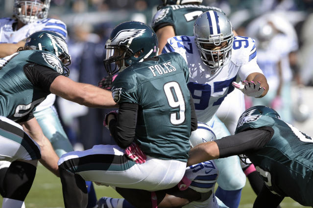 Philadelphia Eagles quarterback Nick Foles (9) is sacked by Dallas Cowboys defensive end George Selvie (99) as defensive tackle Jason Hatcher (97) helps on the play during the first half of an NFL football game, Sunday, Oct. 20, 2013, in Philadelphia. (AP Photo/Michael Perez)