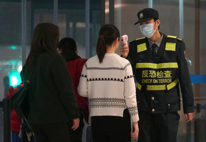 An airport staff member uses a temperature gun to check people leaving Wuhan Tianhe International Airport in Wuhan, China. (AP)