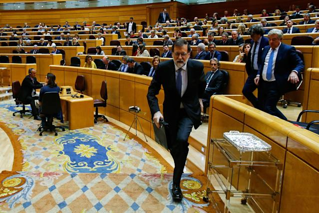 <p>Spain's Prime Minister Mariano Rajoy leaves a session of the Upper House of Parliament in Madrid on Oct. 27, 2017.<br> The central government has invoked the never-before-used article 155 of the Constitution, designed to rein in rebel regions, as it seeks to end Catalonia's drive to break from Spain. Spain's upper house is in charge of approving or rejecting the power seizure of the semi-autonomous Catalonia region proposed by Madrid. (Photo: Oscar del Pozo/AFP/Getty Images) </p>