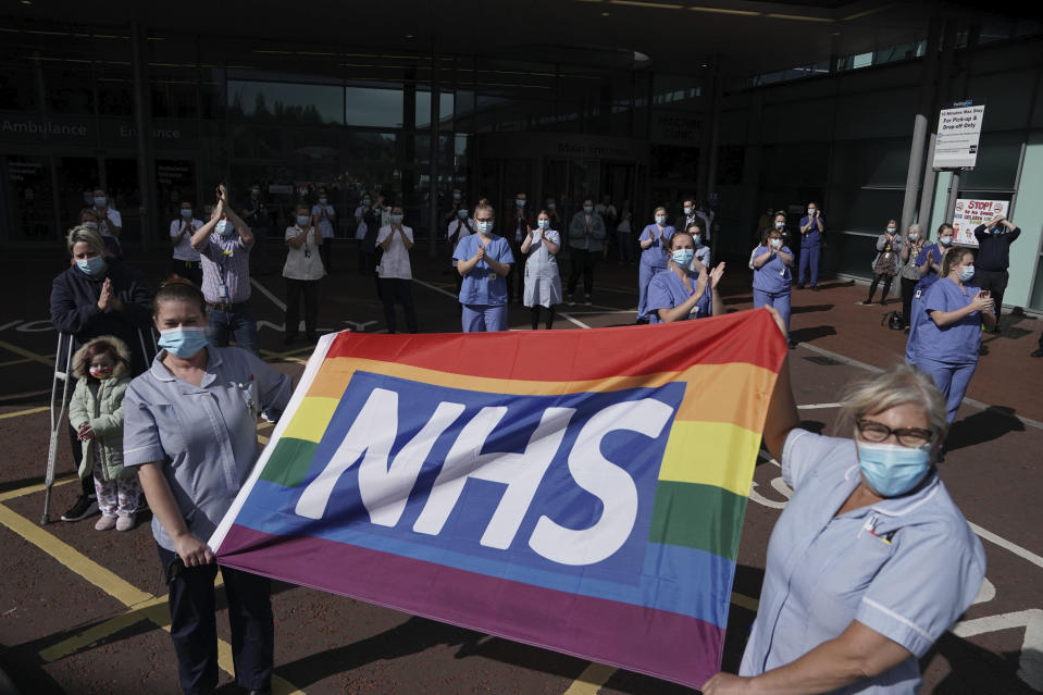 NHS staff outside Royal Victoria Infirmary join in the pause for applause to salute the NHS 72nd birthday, in Newcastle, England, Sunday, July 5, 2020.  People across the U.K. joined a round of applause to celebrate the 72nd anniversary of the formation of the free-to-use National Health Service, undoubtedly the country's most cherished institution. The reverence with which it is held has been accentuated this year during the coronavirus pandemic. (Owen Humphreys/PA via AP)