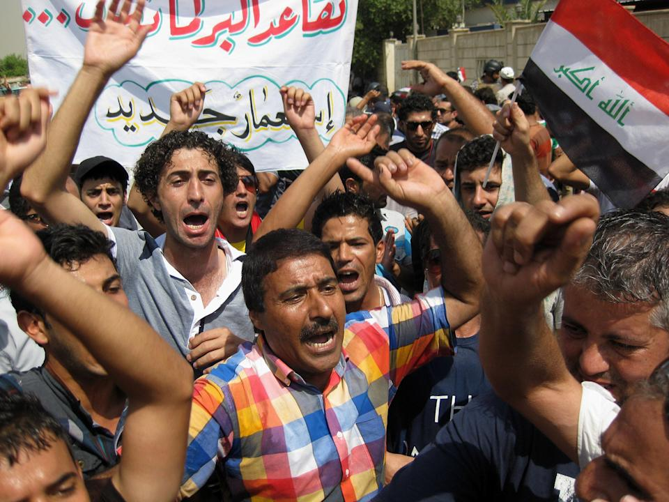"Protesters chant slogans against the Iraqi parliament in Baghdad, Iraq, Saturday, Aug. 31, 2013. Protesters held rallies in Baghdad and the southern Iraqi city of Basra to demand to cancel parliamentarians' pensions. The Arabic on the banner reads, ""Parliamentarians' pensions in a new colonialism."" The Arabic on the Iraqi flag reads, ""God is great."" (AP Photo/ Khalid Mohammed)"
