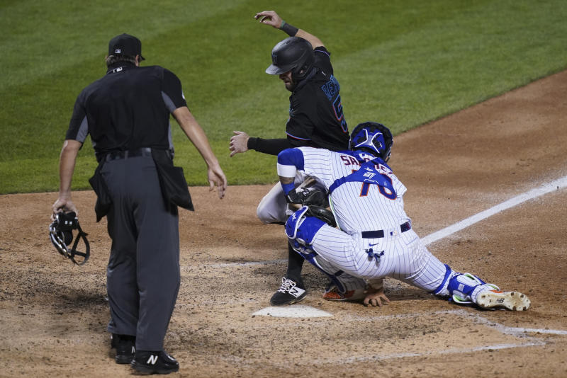 Miami Marlins' Jon Berti, center, steals home against New York Mets catcher Ali Sanchez.