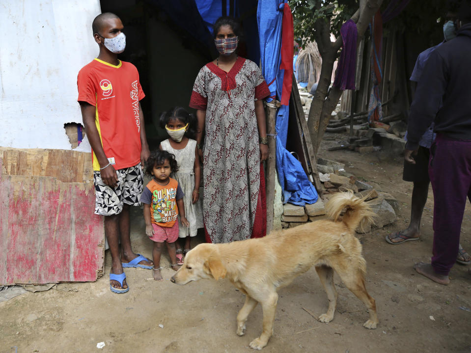 Gangaiah, left, son of Padmavathi who died of COVID-19, stands at the entrance of their family hut with his wife and children in a slum in Bengaluru, India, Thursday, May 20, 2021. Padmavathi collected hair, taking it from women's combs and hairbrushes to later be used for wigs. She earned about $50 a month. (AP Photo/Aijaz Rahi)